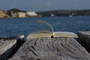 Aufgeschlagenes Buch auf einem Holzsteg an der See